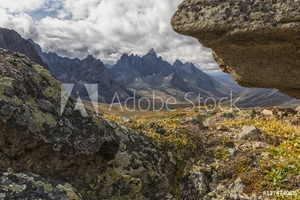 Bild på Tombstone Mountain is framed by rocks in this view within Tombstone Territorial Park; Yukon, Canada