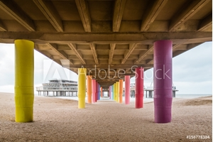 Bild på Shot under pier with color painted columns on the beach at sunset.