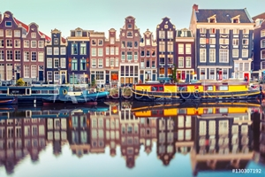 Bild på Amsterdam canal Singel with typical dutch houses and houseboats during morning blue hour, Holland, Netherlands. Used toning