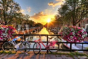 Bild på Beautiful sunrise over Amsterdam, The Netherlands, with flowers and bicycles on the bridge in spring