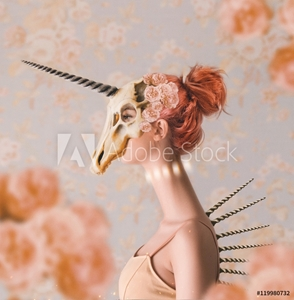 Bild på Woman with long neck wearing unicorn skull on head