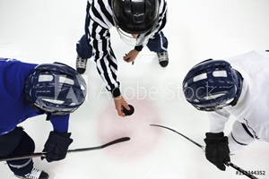 Bild på Directly above shot of referee and two ice hockey players in face-off