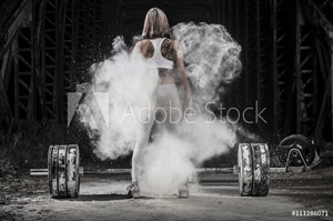 Bild på Woman working out with weights in the gym